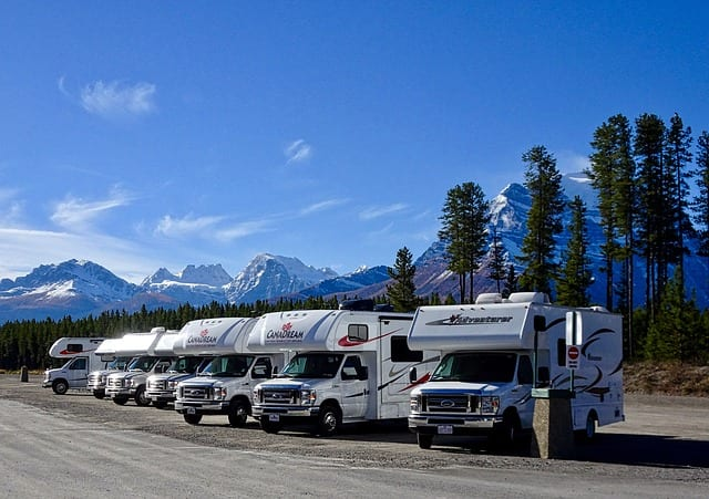 a-row-of-rvs-parked-by-the-road-with-mountains-in-the-background